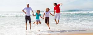 Glad familj hoppar på stranden